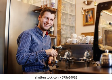 Young smiling man is making coffee with a coffee machine.