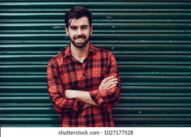 Young smiling man, model of fashion, wearing a plaid shirt with a green blind behind him. Guy with beard and modern hairstyle in urban background.