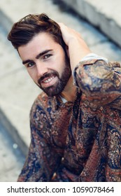 Young smiling man, model of fashion, wearing modern shirt in the street. Guy with beard and modern hairstyle in urban background.