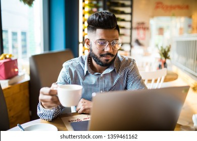 Young smiling man on laptop in cafe