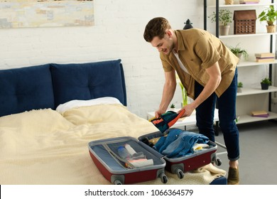 young smiling man packing clothes into travel bag