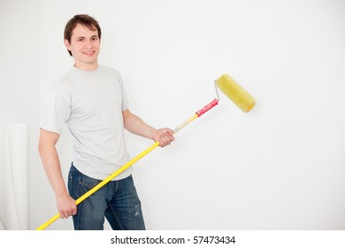 young smiling man painting a wall