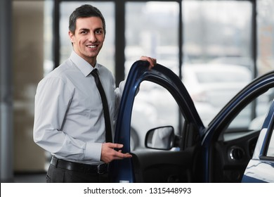 Young smiling man in showroom is standing near car.