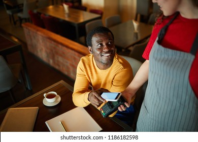 Young smiling man sitting by table and looking at waitress while paying for his order through smartphone