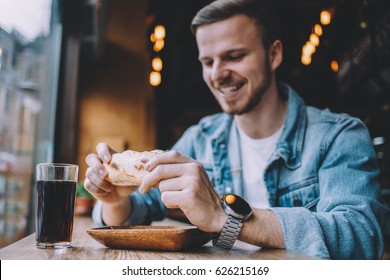 Young smiling man sitting in a cosy restaurant near window at daytime and ready to eat a big sandwich. Attractive freelancer has a lunch during the break