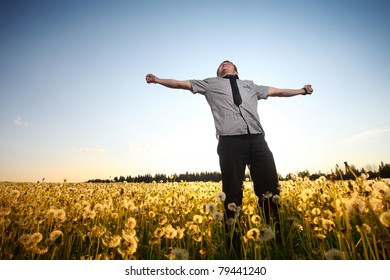 Young smiling man standing on a meadow with dandelions on a blue sky background