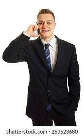 Young smiling man in suit talks into mobile phone