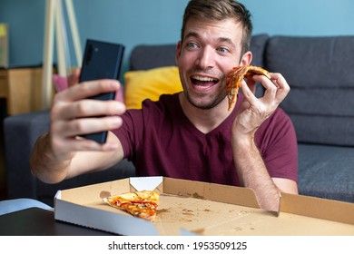 A young smiling man is taking a selfie using a mobile phone and eating pizza at home.