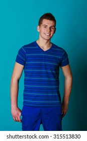 Young smiling man teen boy portrait studio shot on blue background
