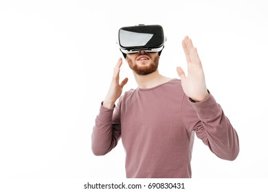 Young smiling man using virtual reality glasses on white background. Portrait of cool boy in fighter stand playing in visual reality glasses isolated
