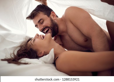 Young smiling man and woman making love in bedroom