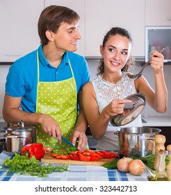 Young smiling man and woman preparing dinner with vegetables at kitchen