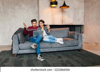 young smiling man and woman sitting at home in winter looking in laptop with surprised shocked face expression, using internet, couple on leisure time together, happy, positive emotion