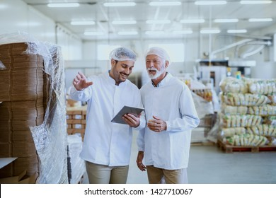Young smiling manager in sterile uniform using tablet for checking goods and talking with employee. Food factory interior.