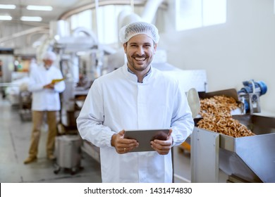 Young smiling manager in sterile uniform holding tablet and looking at camera while standing in food factory.