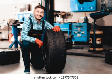 Young Smiling Mechanic Holds A Car Tire At Service Station. Professional Uniform. Confident Engineer Stare. Cheerful Repairman. Working In The Garage. Protective Gloves. Repair Specialist.