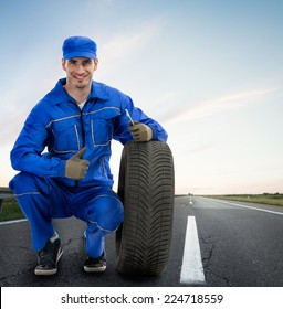 Young Smiling mechanic showing thumbs up next  car tires - road assistance, Towing Service