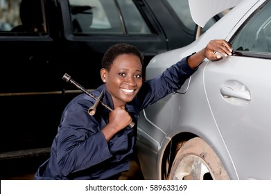Young smiling mechanic squatting near the tire of a car she is preparing to remove.