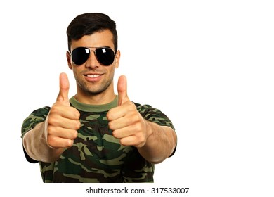Young smiling military man with a sunglasses shows you thumbs up