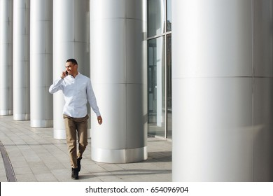 Young smiling mixed race man walking outside and talking phone