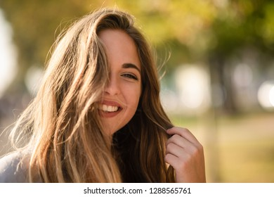 Young smiling model poses while holding her hair
