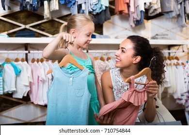 young smiling mother brunette with daughter buying kids clothes in shop