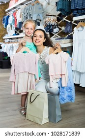 young smiling mother with happy daughter buying kids clothes in shop