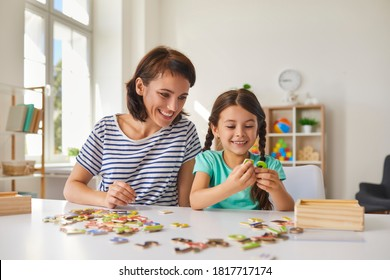 Young smiling mother with her little preschooler daughter make up puzzles while sitting at a table in the room. Concept of childhood, games and leisure.