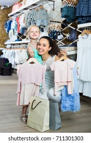 young smiling mother with joyous daughter buying kids clothes in shop
