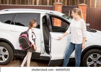Young smiling mother meeting daughter after school lessons