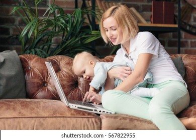 Young smiling mother sitting on sofa while working on laptop at home with one year old baby girl