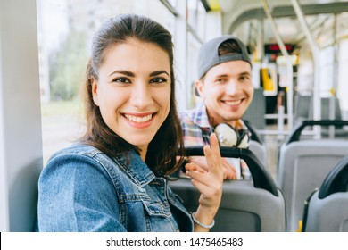 Young smiling multicultural couple, handsome guy and young woman talking while sitting in the city tram. Youth millennial teenager people taking selfie in public transport. Acquaintance concept.