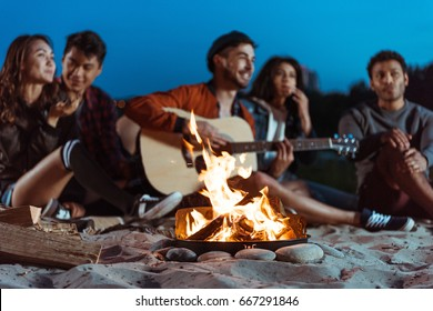 young smiling multiethnic friends spending time near campfire