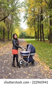 Young smiling mum walks with pram in the autumn yellow park