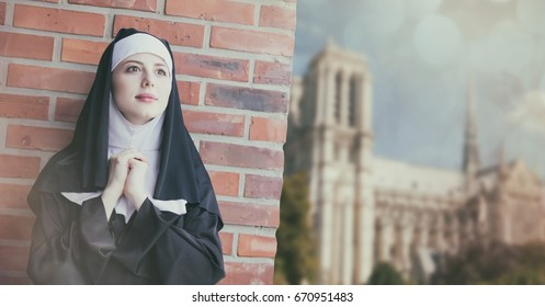 Young smiling nun standing near brick wall and Notre-Dame de Paris on background