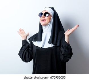 Young smiling nun with sunglasses on white background