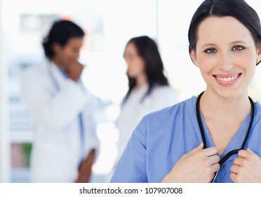 Young smiling nurse standing upright accompanied by her team who is standing behind her