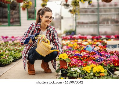 Young smiling nursery garden female worker crouching and watering flowers in pots.