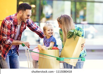 Young smiling parents and their cute daughter with shopping cart full of fresh food having fun in front of hypermarket.