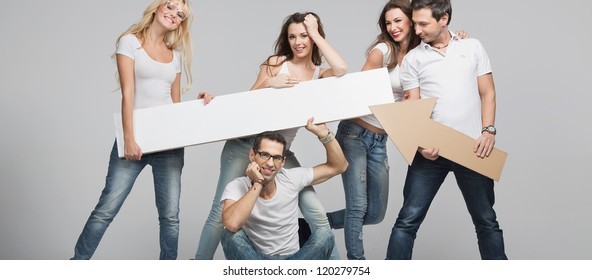 Young smiling people with empty board