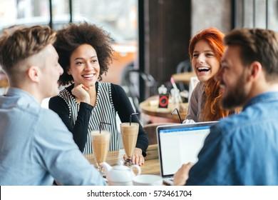 Young smiling people enjoying coffee