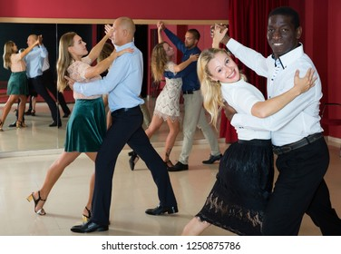 Young smiling people learning to dance waltz in dancing class