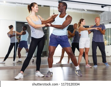 Young smiling people practicing vigorous jive movements in dance class