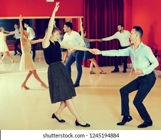 Young smiling people practicing vigorous lindy hop movements in dance class