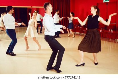 Young smiling people practicing vigorous twist movements in dance class