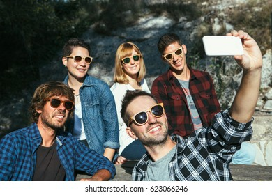 Young smiling people wearing sunglasses taking selfie in park.