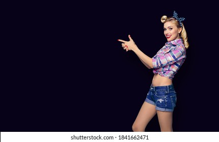 Young smiling pinup woman pointing at something. Excited girl in pin up cloth, showing product or copy space for advertise slogan or ad text. Retro fashion and vintage concept. Black background.