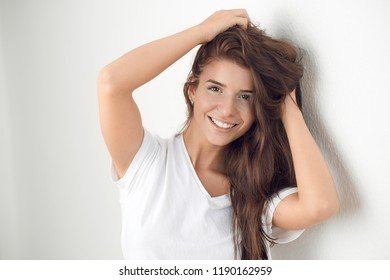 Young smiling playful blond woman holding her hair while leaning against white wall