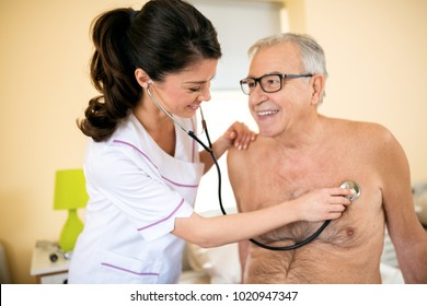 Young smiling positive doctor examining senior patient with stethoscope at nursing home