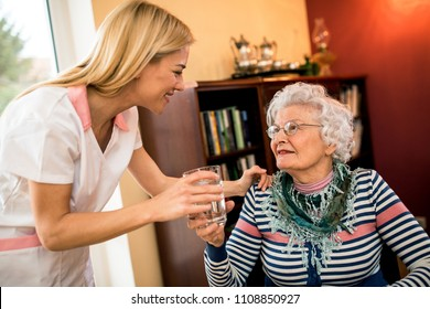 Young smiling positive nurse brings water to old senior patient, full home treatment